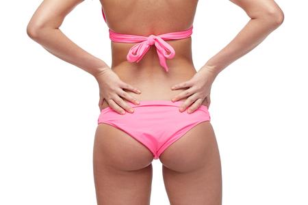 traje de baño: gente, moda, trajes de baño, la playa de verano y el concepto de belleza - cerca de las nalgas de la mujer joven en bikini rosa
