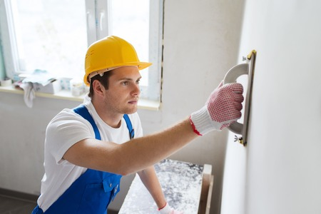 plasterer: business, building, profession and people concept - builder with grinding tool indoors Stock Photo
