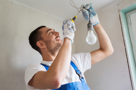 electric bulb: building, renovation, technology, electricity and people concept - builder with screwdriver fixing socket indoors