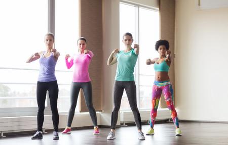 aerobic: fitness, deporte, entrenamiento, gimnasio y artes marciales concepto - grupo de mujeres trabajando y luchando en el gimnasio