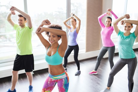 gym girl: fitness, sport, dance and lifestyle concept - group of smiling people with coach dancing zumba in gym or studio