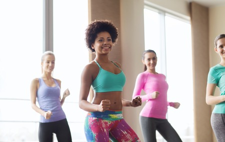 WOMAN FITNESS: fitness, sport, dance and lifestyle concept - group of smiling people with coach dancing zumba in gym or studio