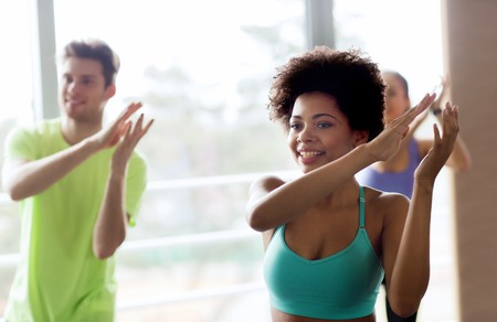 class: fitness, sport, dance and lifestyle concept - group of smiling people with coach dancing zumba in gym or studio