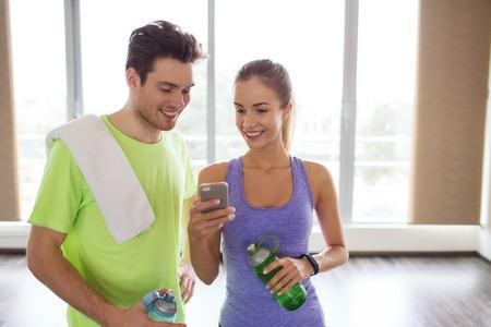 fitness, sport, technologie en vermagering concept - lachende jonge vrouw en persoonlijke trainer met smartphone en flessen water in de sportschool Stockfoto