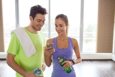 mobile phone: fitness, sport, technology and slimming concept - smiling young woman and personal trainer with smartphone and water bottles in gym Stock Photo