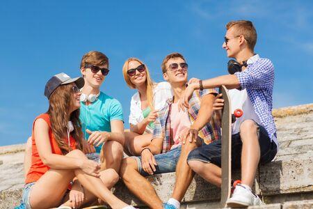 ropa colgada: amistad, ocio, verano y concepto de la gente - grupo de amigos sonriendo con estar patineta en calle de la ciudad