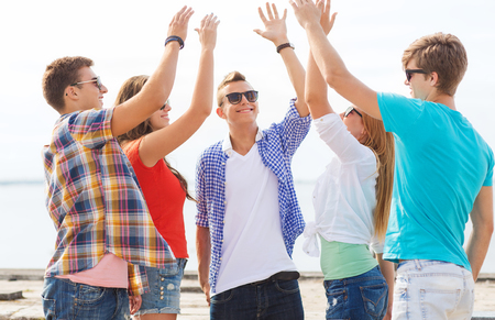 beautiful boys: friendship, leisure, summer, gesture and people concept - group of smiling friends making high five outdoors