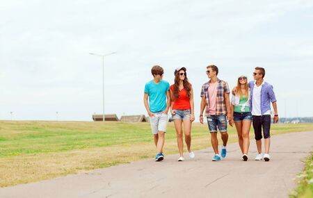 teen: holidays, vacation, love and friendship concept - group of smiling teenagers walking outdoors