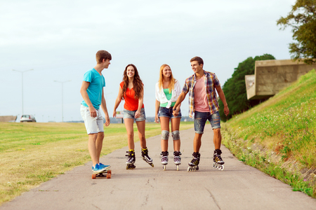 friendship: holidays, vacation, love and friendship concept - group of smiling teenagers with roller skates and skateboard riding outdoors