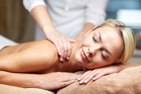 spa woman: people, beauty, spa, healthy lifestyle and relaxation concept - close up of beautiful young woman lying with closed eyes and having hand massage in spa