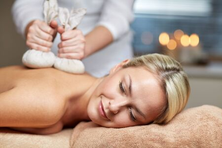 massagist: people, beauty, spa, healthy lifestyle and relaxation concept - close up of beautiful young woman lying and having herbal bag massage in spa Stock Photo