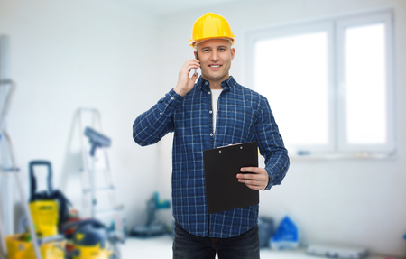 storeroom: repair, building, construction and maintenance concept - smiling man or builder in helmet with clipboard calling on smartphone over storeroom background