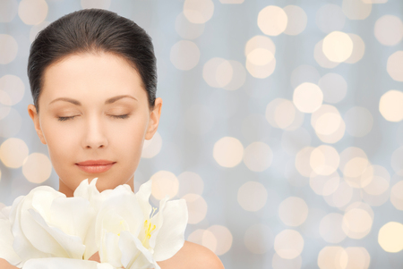 beauty, people, holidays and health concept - beautiful young woman smelling flowers with closed eyes over lights background Foto de archivo