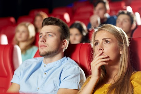 horror movie: cinema, entertainment and people concept - happy friends watching horror, drama or thriller movie in theater