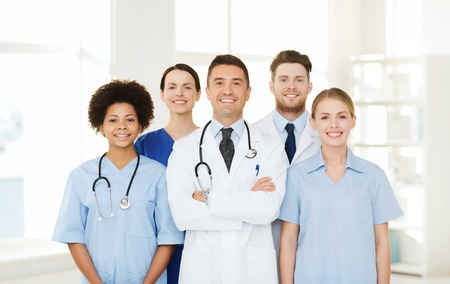 hospital, profession, people and medicine concept - group of happy doctors at hospital. Stock Photo