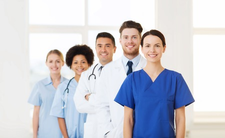 clinics: hospital, profession, people and medicine concept - group of happy doctors at hospital