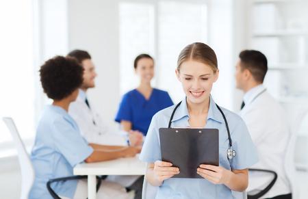 sano: cl�nica, la profesi�n, la gente y concepto de la medicina - feliz m�dico femenino sujetapapeles sobre grupo de m�dicos reunidos en el hospital