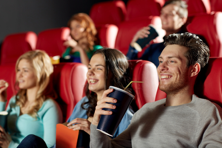 food and drink industry: cinema, entertainment and people concept - happy friends watching movie in theater
