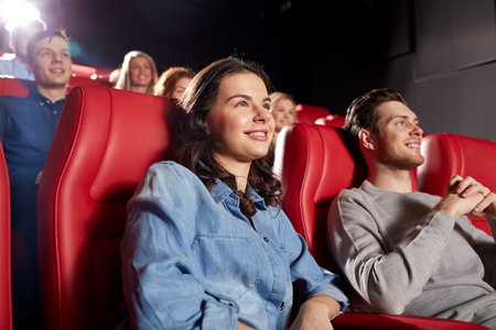 film: cinema, entertainment and people concept - happy friends watching comedy movie in theater