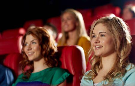 asiento: el cine, el entretenimiento y la gente concepto - amigos felices viendo la película en el teatro