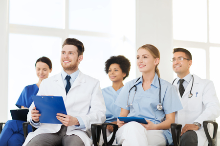 medics: hospital, profession, people and medicine concept - group of happy doctors on seminar in lecture hall at hospital