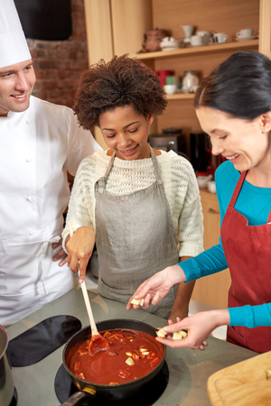 cooking ingredients: cooking class, culinary, food and people concept - happy group of women and male chef cook cooking tomato souse in kitchen