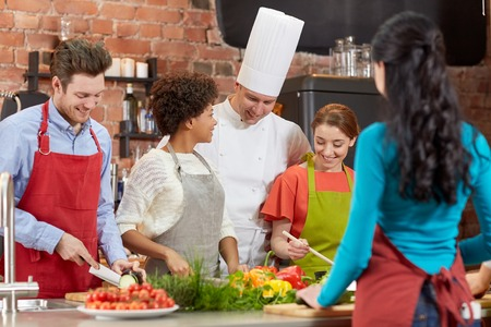 multiracial family: cooking class, culinary, food and people concept - happy group of friends and male chef cook cooking in kitchen Stock Photo