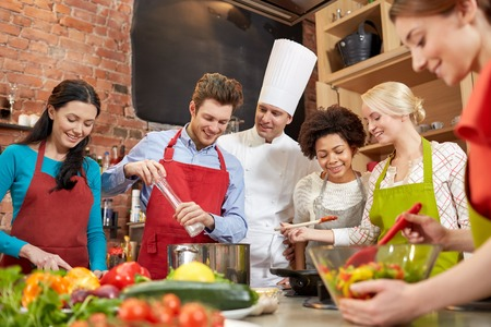 courses: cooking class, culinary, food and people concept - happy group of friends and male chef cook cooking in kitchen Stock Photo