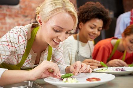 cooking: cocinar clase, la amistad, la comida y la gente concepto - mujeres felices de cocina y platos de decoraci�n con los platos en la cocina