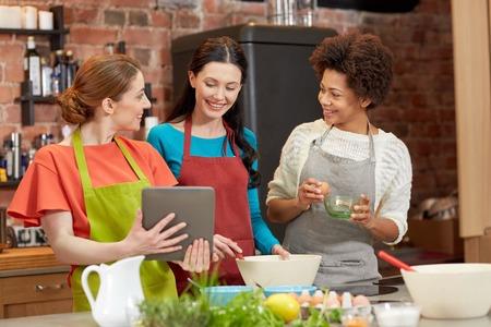 mujeres cocinando: clase de cocina, la amistad, la comida, la tecnología y la gente concepto - mujer feliz con ordenador Tablet PC en la cocina