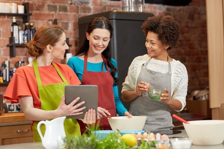 women friendship: cooking class, friendship, food, technology and people concept - happy women with tablet pc computer in kitchen