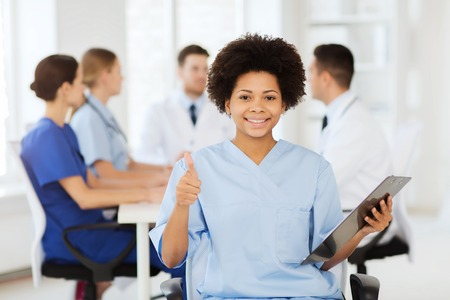 saludable: clinic, profession, people and medicine concept - happy female doctor or nurse with clipboard over group of medics meeting at hospital showing thumbs up gesture