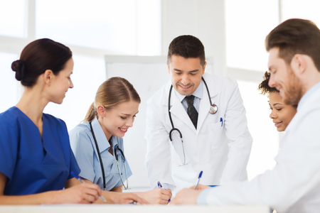 doctor office: hospital, profession, people and medicine concept - group of happy doctors meeting and taking notes at medical office