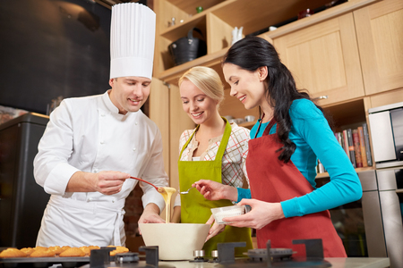 cooking: cooking class, culinary, bakery, food and people concept - happy group of women and male chef cook baking muffins in kitchen