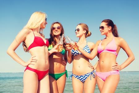 chica sexy: las vacaciones de verano, las vacaciones, los viajes y el concepto de la gente - grupo de mujeres jóvenes sonrientes tomando el sol y bebiendo en la playa