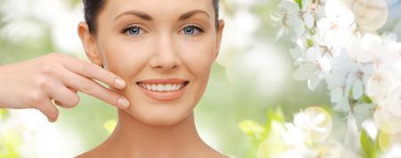 医療・人・美容コンセプト - 緑の夏庭と桜の花の背景に彼女の顔の皮膚に触れる美しい女性