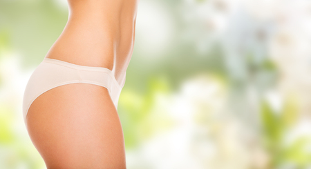 people, health, body care and beauty concept - close up of slim woman tummy and hips in underwear over green background