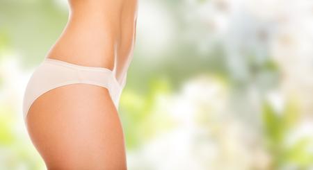 mensen, gezondheid, lichaamsverzorging en schoonheid concept - close-up van slanke vrouw buik en heupen in ondergoed over groene achtergrond Stockfoto