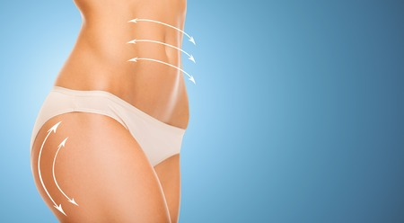 slimming: people, health, body care and beauty concept - close up of slim woman tummy and hips in underwear over blue background