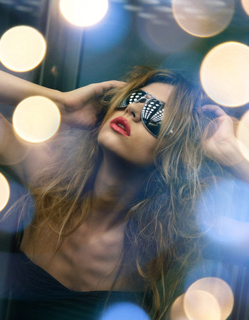 fashion and people concept - beautiful woman in sunglasses in elevator photo