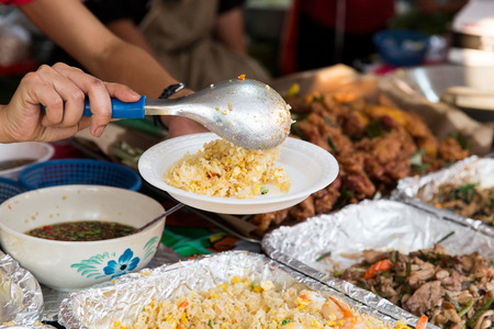 food sales: cooking, asian kitchen, sale and food concept - close up of hands with plate, spoon and wok at street market Stock Photo