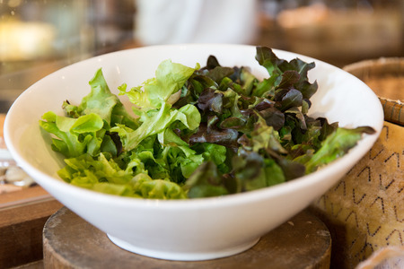 cooking, kitchen and food concept - bowl of green salad lettuce at asian restaurant