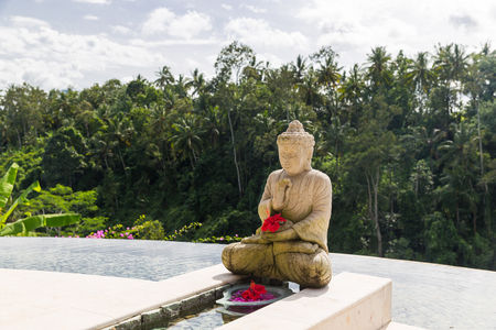 infinity: travel, vacation, tourism, religion and luxury concept - beautiful view from infinity edge pool with buddha statue to tropical woods in asia Stock Photo