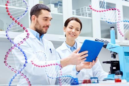ciencia, química, tecnología, biología y concepto de la gente - los científicos jóvenes con Tablet PC y microscopio haciendo pruebas o investigación en laboratorio clínico