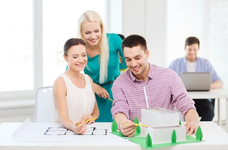 design interior: startup, education, architecture and office concept - smiling architects with house model and blueprint working in office Stock Photo