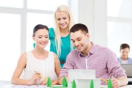 architects: startup, education, architecture and office concept - smiling architects with house model and blueprint working in office Stock Photo