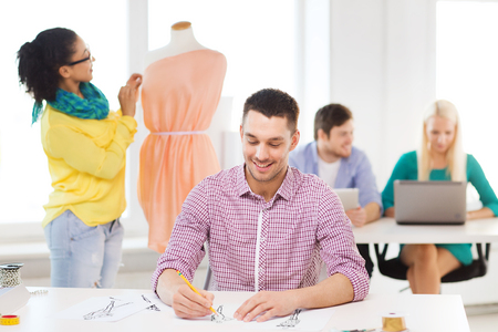 adjusting: startup, education, fashion and office concept - smiling male drawing sketches and female adjusting dress on mannequin in office