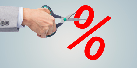 cutting costs: business, people, financial crisis, sale and default concept - close up of businessman hand with scissors cutting percents over gray background