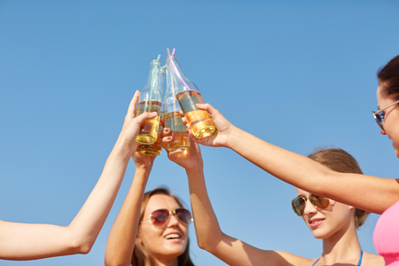 nonalcoholic beer: summer vacation, holidays, party, travel and people concept - close up of happy young women with drinks clinking bottles