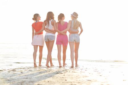 ropa colgada: las vacaciones de verano, las vacaciones, los viajes, la amistad y la gente concepto - grupo de mujeres jóvenes caminando en la playa Foto de archivo